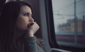 teen looking wistfully out a window