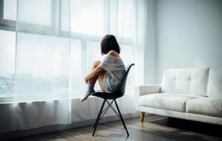 girl sitting on chair looking out window, coping with loneliness